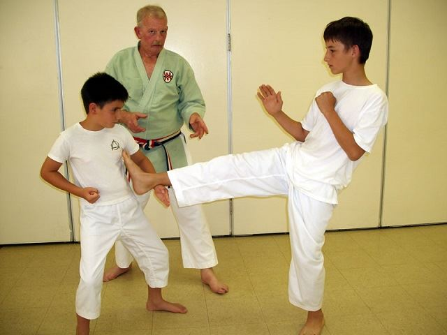 Boys practice martial arts as an instructor looks on